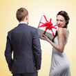 Man looking on smiling woman holding gift