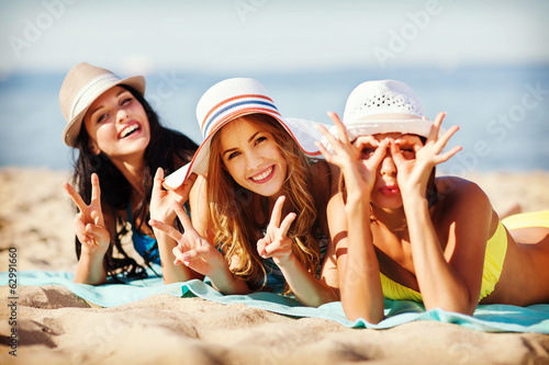 girls sunbathing on the beach - 62991660
