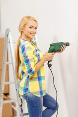woman with electric drill making hole in wall