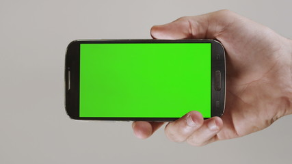 Generic smarth phone without a logo enters the screen by a hand.