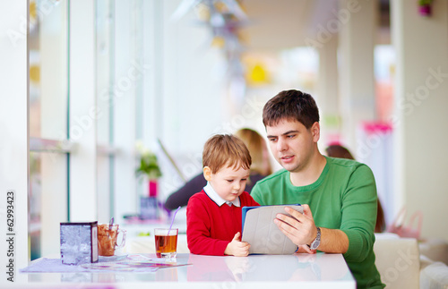 father and son with tablet in colorful cafe