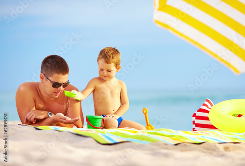 happy father and child playing in sand on the beach