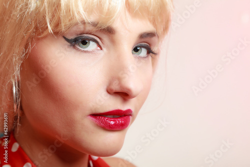 Portrait pinup girl in blond wig and retro makeup. Vintage.
