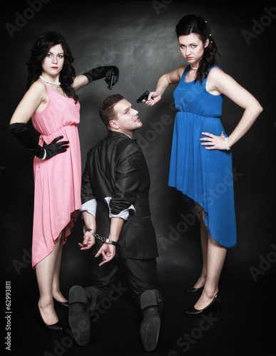 Two elegant women with gun gangster in handcuffs