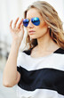 Outdoor portrait of fashionable young woman in sunglasses - clos