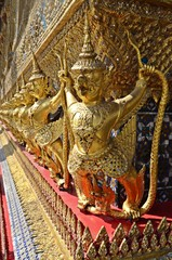 golden statues on the wall of the Grand Palace