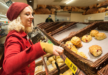 young woman buying scones at bakery
