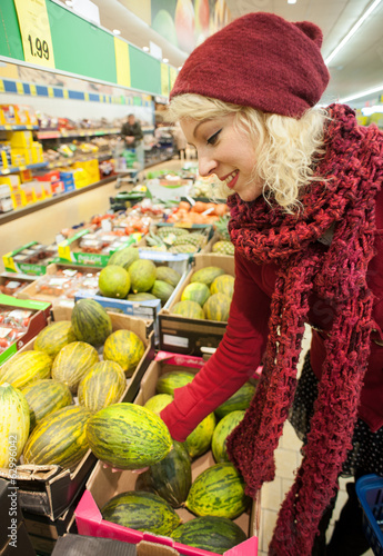 young female customer buying melon at supermarket