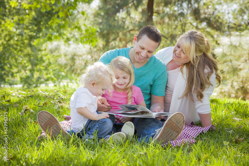 Young Family Enjoys Reading a Book in the Park