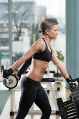 Young Woman Exercising Triceps With Dumbbell