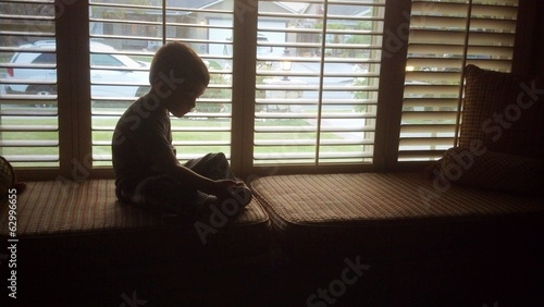 Young boy silhouetted plays in the window seat.