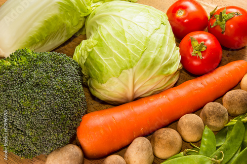 Variety of fresh vegetables on wooden table