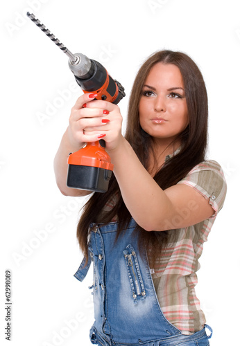 Young woman holding a cordless electric drill. Isolated on white