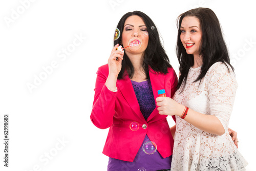 Women friends blow out bubbles