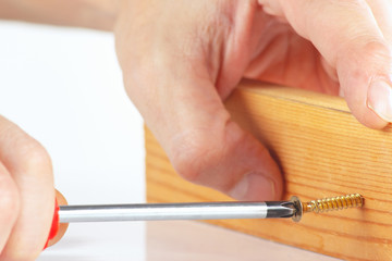 Hand of repairman screws in a wooden block with a screwdriver