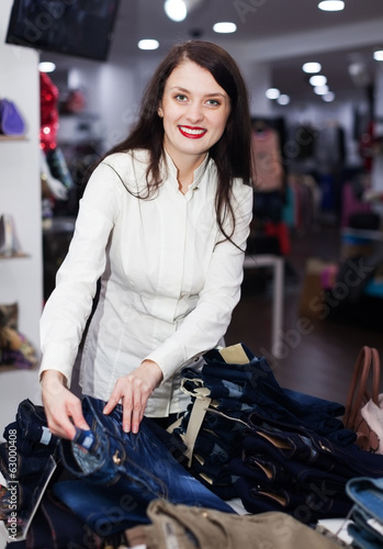 Young woman choosing jeans at store