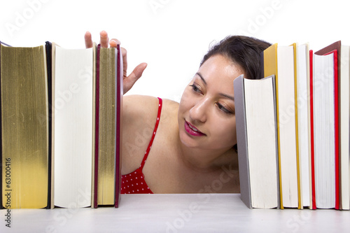 woman reading books from a bookshelf seen in front view
