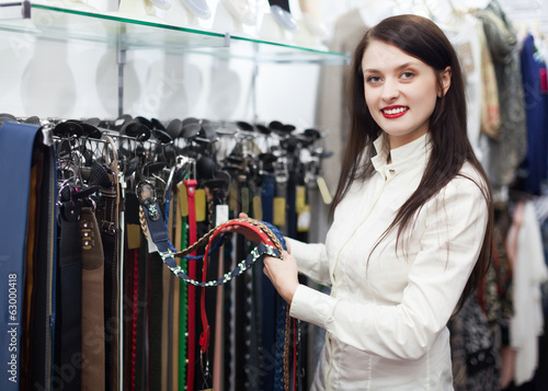 woman  chooses  belt at shop