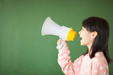 happy kid using a megaphone to shout