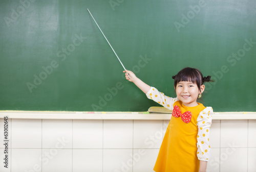 little girl using a baton to point on a blackboard
