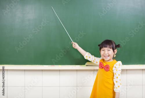 smiling girl using a baton to point on a blackboard