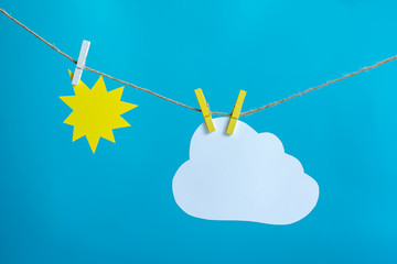 Sun and cloud hanging on a rope