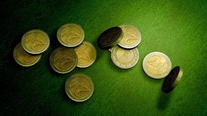 Euro coins falling on a green velvet table
