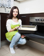Girl with cake near  oven