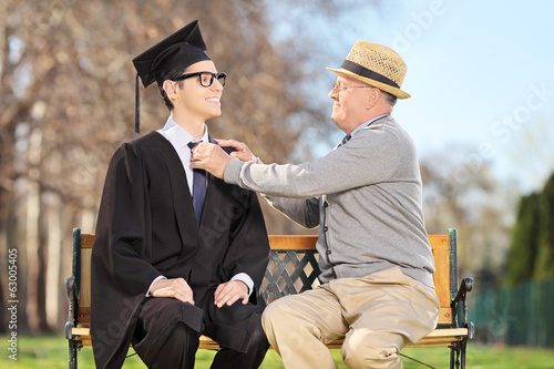 Father preparing his son for graduation in park