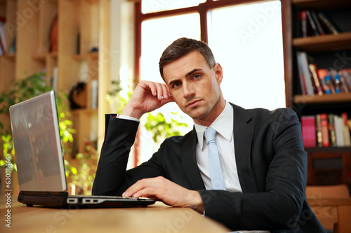Confident businessman sitting with laptop at office