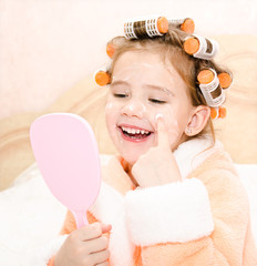 Happy cute little girl in hair curlers with mirror applying crea
