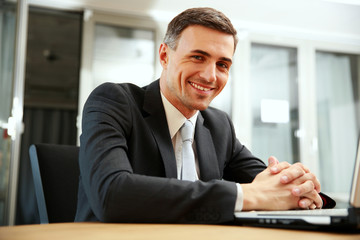 Happy businessman sitting with laptop at office