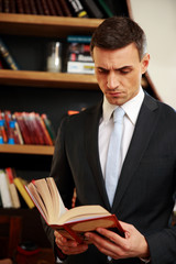 Businessman reading the book in library