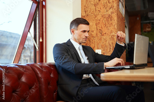 Businessman sitting and using laptop at office