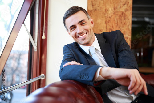 Smiling businessman sitting at the sofa in office