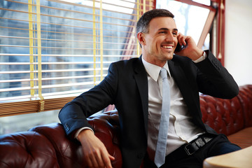 Smiling businessman sitting and talking on the phone at office