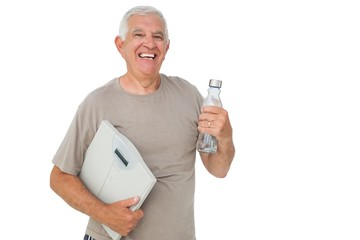 Cheerful senior man with water bottle and scales