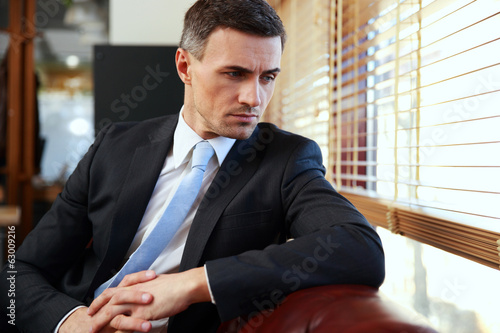 Pensive businessman sitting and looking in window at office