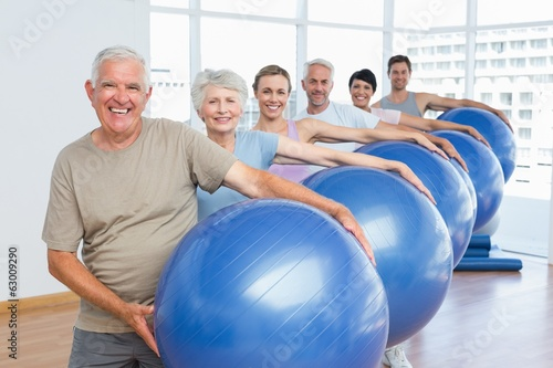 Sporty people carrying exercise balls in bright gym