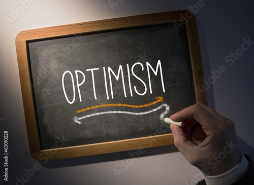 Hand writing Optimism on chalkboard