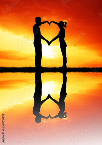 couple and heart at sunset