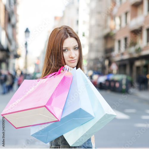 Attractive young woman with shopping bags in the street.