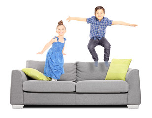 Boy and a girl jumping on the couch