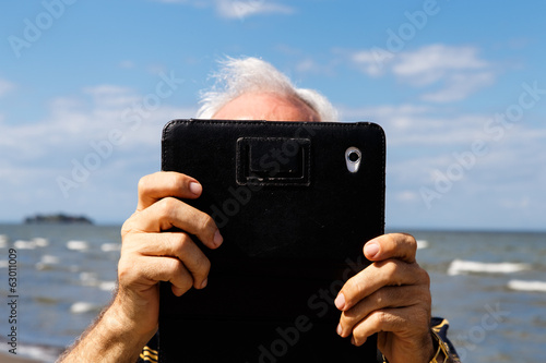 photography of a man using tablet