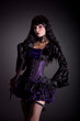 Beautiful witch in purple and black gothic Victorian outfit