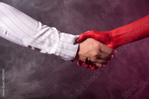 Businessman making an agreement with devil