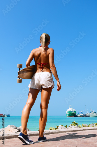 woman walking and holding a longboard
