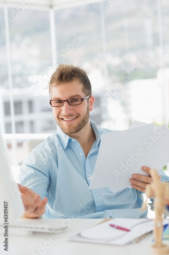 Handsome designer sitting at his desk gesturing at camera