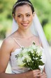 Smiling young beautiful bride with bouquet in park