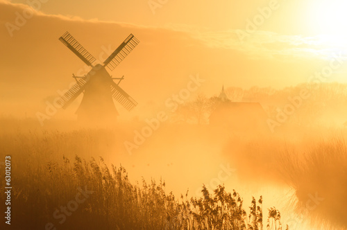 Windmill and foggy sunrise